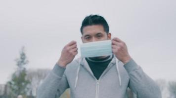 jeune homme asiatique, debout, dehors, mettre, masque visage video