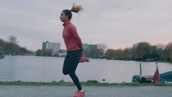 Black young woman in park, waterfront, doing physical exercise, running movements on same place, turning and running with feet touching hands, held on back video