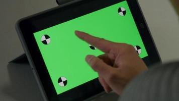 dedo do jovem asiático se move na frente da tela verde do tablet. video
