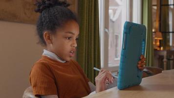 Girl sits at table, holds tablet with one hand in front of her, stylus pen in other hand making lines on screen. Talks, turning her head and turns head back, twice video
