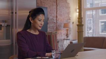 mulher asiática madura se senta à mesa na cozinha, enquanto digita no laptop, movendo a cabeça para a tela e para trás, e olhando para cima video