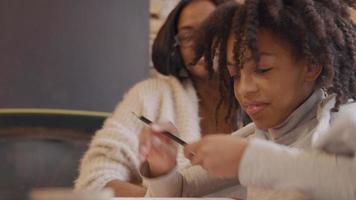 mujer y niña se sientan a la mesa. niña elige lápiz de color, lee en el libro de trabajo frente a ella. la mujer señala el libro, el dedo índice sigue las líneas, mientras lleva a la niña.