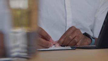 mãos de homem maduro, escrevendo, pressionando papel, rosto de homem observando com foco nas mãos, virando a cabeça para a luz do laptop - laptop não mostrado video