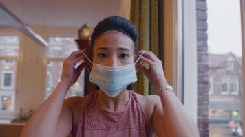 mulher asiática olha pela janela, vira-se para a câmera, coloca máscara e sai video