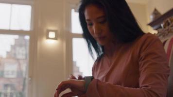 mulher sentada na poltrona, olhando pela janela, virando a cabeça, olhando no smartwatch video