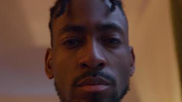 närbild av svart man, ögonen något nedåt, efter kameran