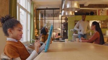 garota se senta à mesa, segura o tablet com uma mão na frente dela e a caneta stylus na outra mão. no fundo homem maduro em pé e duas mulheres maduras sentadas à mesa, conversando. menina continua assistindo tablet enquanto desenha e coça na tela. ela sorri,...