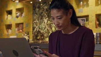 asiatische Frau sitzt in der Küche und beobachtet, hält und berührt den Bildschirm des Handys. Laptop vor