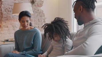 Frau, Kind und Mann sitzen auf der Couch. Mädchen, das in der Mitte sitzt, ist mit Kindertabletten beschäftigt, Mann und Frau sprechen mit ihr