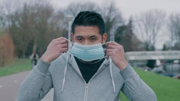 jovem asiático parado do lado de fora, colocando máscara