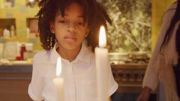 la ragazza guarda due candele accese davanti a lei, ne spegne una. l'altra candela ha bisogno di tre tentativi, la ragazza ride e fa un passo indietro