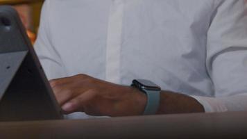 mão de homem maduro digitando no laptop, levanta o braço com smartwatch, tocando em smartwatch, rosto de homem focado em smartwatch video
