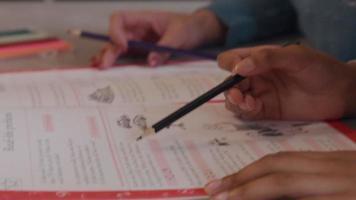 Cerca de las manos de la niña, sosteniendo un lápiz y un libro de trabajo sobre la mesa