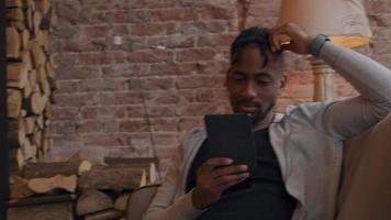 homem maduro se senta no sofá, assistindo e segurando o tablet com uma mão na frente dele. outra mão toca a cabeça video