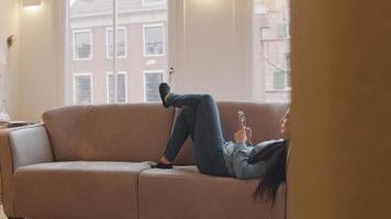 mujer en el sofá, la cabeza en el apoyabrazos, las piernas dobladas, cruzadas en el sofá. sostiene el teléfono móvil frente a ella, desplazándose.