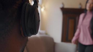 close-up da parte direita da parte de trás da cabeça de um homem maduro com fone de ouvido na orelha. mulher madura entra, senta-se no sofá, falando nervosamente, movendo os braços e as mãos com destaque. homem tira fone de ouvido