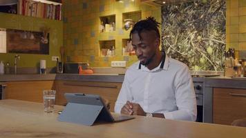 volwassen man zit aan de keukentafel, laptop voor zich, videogesprek video
