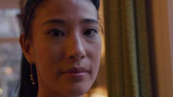 Cerca de la mujer asiática delante de la ventana, girando la cabeza hacia la cámara
