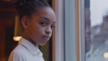 garota negra em frente à janela, cabeça e olhos voltados para a câmera, parecendo sérios