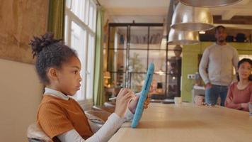 garota se senta à mesa, segura o tablet com uma mão na frente dela e a caneta stylus na outra mão. no fundo homem maduro em pé e mulher madura sentada à mesa, conversando. garota observa as pessoas, olha para a câmera, olha para as pessoas e a tela