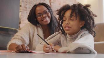 mujer se sienta junto a la niña en la mesa. mujer habla con niña, mientras que la niña escribe en el libro de trabajo con lápiz. ambos sonriendo. la mujer señala en el libro de trabajo, la niña piensa, la niña sigue escribiendo.