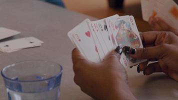 feche as mãos de uma mulher, segurando cartas de baralho, tirando uma carta da pilha, adiciona uma carta a outras cartas e bate na mesa duas vezes video