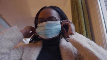 mujer de espalda con gafas, se pone mascarilla, se ajusta video