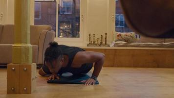 svart man tränar armhävningar med alternerade böjda ben på mattan