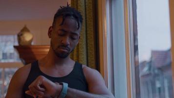 zwarte man kijkt naar smartwatch, veegt en tikt erop, terwijl hij knikt, fronsend, glimlachend.