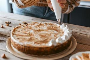 Woman putting whipped cream on cake