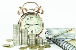 monedas apiladas con reloj despertador