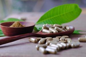 Cápsula de píldora de hierbas en la mesa de madera con hojas verdes foto