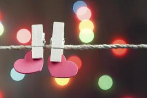 Two clothes pins holding red hearts on rope photo