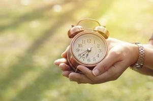 Person holding an alarm clock photo