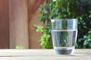 Vaso de agua potable sobre fondo de madera foto