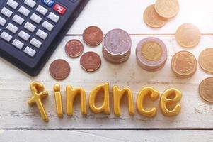 Finanzas palabra sobre mesa de madera con monedas
