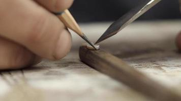 sculpteur sur bois dessine des marques avec un crayon