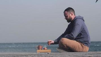 Bearded Man Drinks Chinese Tea at a Pier by the Sea