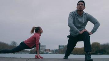 jovem negra e jovem asiático no parque, numa plataforma de madeira, à beira-mar, fazendo exercícios físicos, esticando uma perna para trás e a outra dobrada para a frente