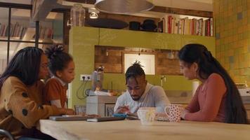 un hombre niña y dos mujeres se sientan alrededor de la mesa mirando al hombre que se desplaza y toca el dispositivo para niños