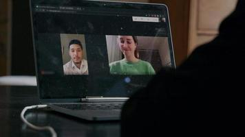 Video-call on screen of laptop, with one Asian young man and one white woman