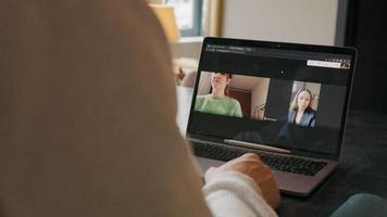 rechte Hand des jungen Mannes, der Hand auf Mauspad bewegt, zwei Frauen auf Laptop-Bildschirm, die Videoanruf haben video