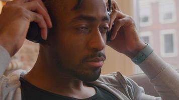 homem maduro senta e coloca o fone de ouvido nos ouvidos, movendo a cabeça lentamente no ritmo video