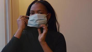 Woman looks, eyes down, holds face mask in front of her, talks, puts down mask and up again, looking into camera, putting it on het face, adjusting mask