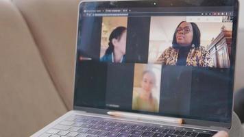 close up da tela do laptop com videochamada com três mulheres em três quadros mostrados video