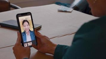 Woman holds cell phone in front of her, sitting at table, having video call
