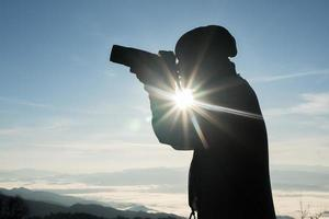 Silhouette of young photographer holding a camera with mountain landscape photo