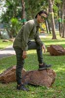Retrato de feliz joven asiático en camisa de manga larga y pantalón verde de pie en el parque