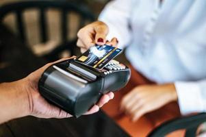 Close-up de mujer pagando con tarjeta de crédito en el café