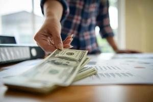 Young business woman checks dollar banknotes